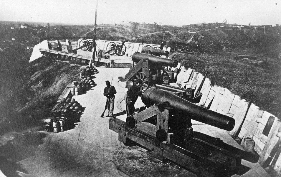 Two Union soldiers attending a battery of cannons.
